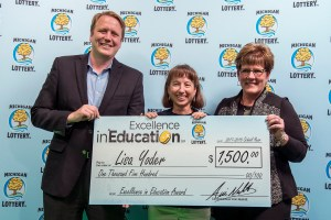 Lisa Yoder (center) poses for a photo with Michigan Lottery Commissioner, Aric Nesbitt, and colleague, Wendy Giles, after accepting her Excellence in Education Award.