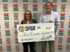 Bev Brooks is presented with a check for $64,940 by Lottery Commissioner, Aric Nesbitt.
