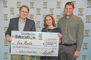 Erin Martin poses for a photo with her husband, Art Martin, and Michigan Lottery Commissioner, Aric Nesbitt, after accepting her Excellence in Education Award.