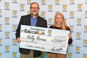 Holly Hereau poses for a photo with Michigan Lottery Director of Public Relations, Jeff Holyfield, after accepting her Excellence in Education Award.