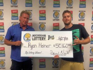Ryan Hainer (right) and his father, Joel, smile after collecting Ryan's Club Keno The Jack prize on Monday.