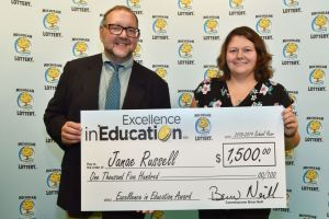 Janae Russell poses for a photo with Michigan Lottery public relations director, Jeff Holyfield, after accepting her Excellence in Education Award.