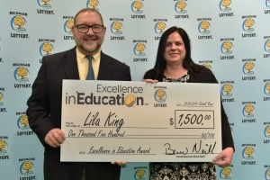 Lila King (right) poses for a photo with Michigan Lottery public relations director, Jeff Holyfield, after accepting her Excellence in Education Award.
