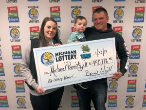 Micheal Parnick, Jr. poses for a photo with his wife, Ashley, and son, Carter, after claiming his $490,776 jackpot.