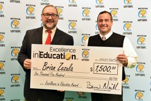 Brian Zezula (right) poses for a photo with Michigan Lottery public relations director, Jeff Holyfield, after accepting his Excellence in Education Award.