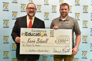 Kevin Bidwell (right) poses for a photo with Michigan Lottery public relations director, Jeff Holyfield, after accepting his Excellence in Education Award.