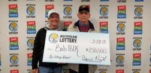 Bob Polk (right), and his stepson, Bryan, pose for a photo after collecting Bob's $250,000 prize.