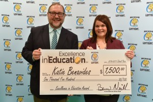 Katie Benavides (right) poses for a photo with Michigan Lottery public relations director, Jeff Holyfield, after accepting her Excellence in Education Award.