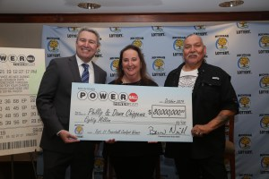Michigan Lottery Commissioner, Brian O. Neill (left), presents Powerball jackpot winners, Phillip and Dawn Chippewa, with a check for $80 million,