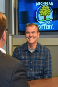Kevin Cousino is interviewed after being presented with an Excellence in Education award from the Michigan Lottery.