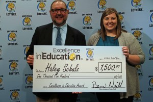 Haley Schulz Cucinello (right) poses for a photo with Michigan Lottery public relations director, Jeff Holyfield, after accepting her Excellence in Education Award.