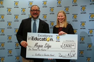 Megan Sidge (right) poses for a photo with Michigan Lottery public relations director, Jeff Holyfield, after accepting her Excellence in Education Award.