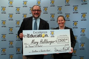 Mary Hulliberger (right) poses for a photo with Michigan Lottery public relations director, Jeff Holyfield, after accepting her Excellence in Education Award.
