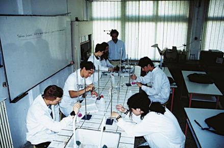 """Το Χημείο του σχολείου μας. Στο Πολυκλαδικό δεν κάναμε """"χαρτοχημεία"""". Οι μαθητές φοράνε εργαστηριακές μπλούζες και εκτελούν μόνοι τους τα πειράματα. Ο εκπαιδευτικός - Γ. Ζωγλοπίτης στην άκρη του πάγκου παρακολουθεί. Όπως και στο σχολείο του Κουντουρά, η διδασκαλία δεν γίνεται από """"καθέδρας""""."""