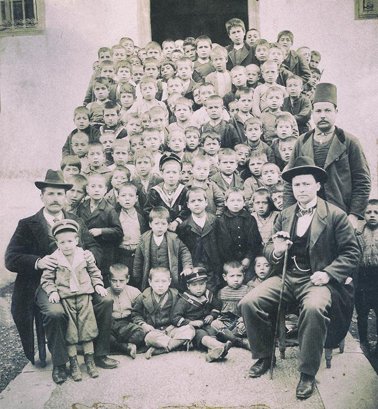 """Φεβρουάριος 1903. Δημοτικό Σχολείο Σκοπέλου Γέρας. Ο μαθητής Παναγιώτης Γ. Κουντουράς, μικρότερος αδελφός του Μίλτου Κουντουρά, όρθιος, πίσω ακριβώς από το καθιστό, στην πρώτη σειρά, παιδάκι με το """"ναυτικό"""" καπέλο. Φωτογράφος : Ι. Γ. Φεργαδιώτης, Φωτογράφος Σμύρνης."""