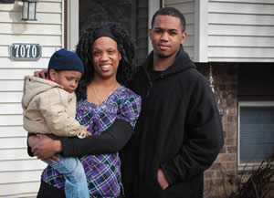 Jerrina McBride and her sons Zyaire and Malik stand proudly in front of their new home, which she purchased with the help of the Make Your Money Talk program.