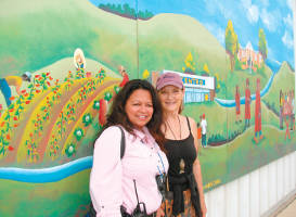 Gloria Reyes (left) with Sharon Kilfoy in front of a mural at Centro Hispano