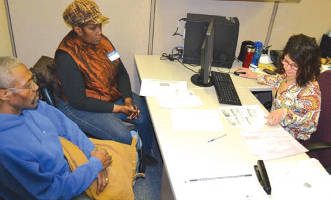 Tax Preparer Susana Azcueta fills out taxes for two Milwaukee residents during an earlier Super Saturday at SDC.