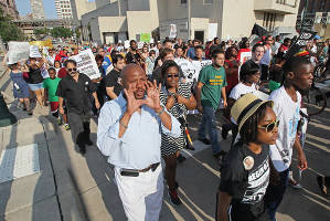 People march down State St. to the Municipal Court and Police Administration buildings to deliver demands after a rally at Red Arrow Park, where a Milwaukee officer shot Dontre Hamilton, a mentally ill man, earlier this summer. Photo by Michael Sears