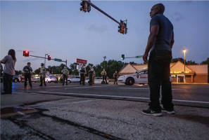A local man from Canfield Green Apartment Complex had an inadvertent face-off with local police at West Florissant and Ferguson avenues while trying to get home on Monday. (Lawrence Bryant/ St. Louis American)