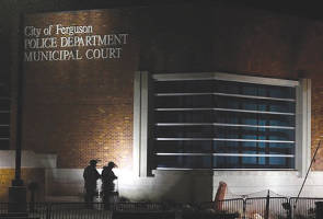 In this Nov. 26, 2014, fi le photo, nembers of Missouri National Guard stand outside of the Ferguson Police Department and the Municipal Court in Ferguson, Mo. (AP Photo/Jeff Roberson, File)