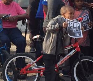 young-man-riding-bike-holding-signs-stop-gun-violence-police-shooting-people