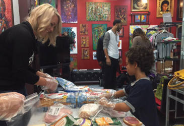 Lloyd Johnson's young son Gabe helps a volunteer make sandwiches for homeless individuals. Photo by Ariele Vaccaro.