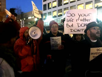 Jennifer Epp-Addison (far left) and Rev. Steve Jerbi (far right) call for a federal investigation into MPD with Coalition for Justice and the family of Dontre Hamilton on Thursday evening during the city Christmas tree lighting.