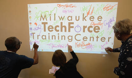 Community Members sign the wall using a Smart Board in one of the TechForce Center classrooms. Photo by Pat Robinson
