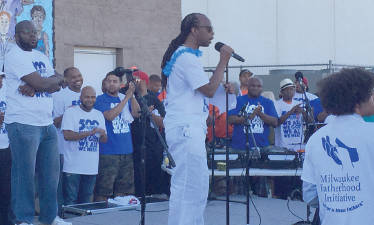 Dennis Walton surrounded by fathers who pledged to help stop the violence in the community. (Photo by Dylan Deprey)