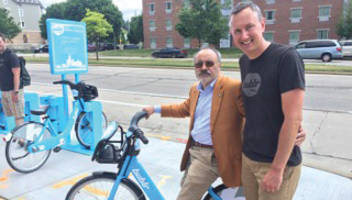 Tony Perez, executive director or Housing Authority of City of Milwaukee tries out a Bublr Bike and poses with Kevin Hardman, executive director of Bublr Bikes. Photo By Bublr Bikes