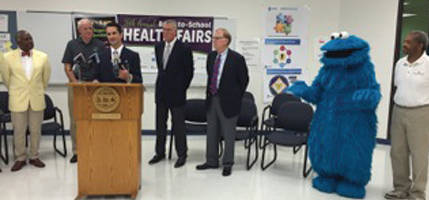 Health Commissioner Bevon Baker, Mayor Tom Barrett, United Healthcare's Ryan Heath, Molina Healthcare Dental Director John Busby, Molina Healthcare President Scott Johnson, Cookie Monster and Milwaukee Urban Leauge President and CEO Ralph Hollman during a press conference. (Photo by Dylan Deprey)
