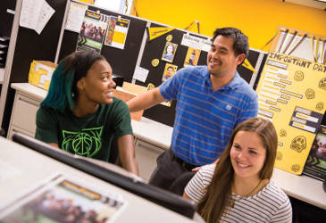 Chue Vang consults with colleagues Brianna Suggs (left) and Marlee Giacometti (right). Vang is a full-time financial-aid advisor at UWM. Suggs and Giacometti are student workers in the financial aid office.