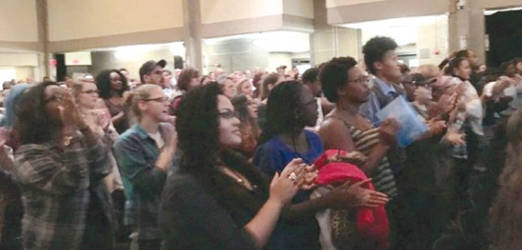 The room was packed. The crowd welcomes the speakers to stage with a standing ovation. (Photo by Angeline Bergman)