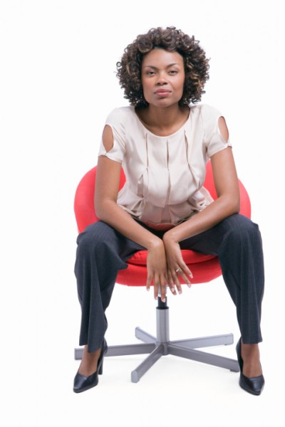 Young woman sitting in chair against white background, portrait