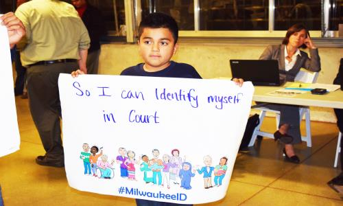 A young supporter of county-issued photo identification card holds up a sign at the Milwaukee County Board of Supervisors budget hearing November 2, 2015 at the Mitchell Park Domes.