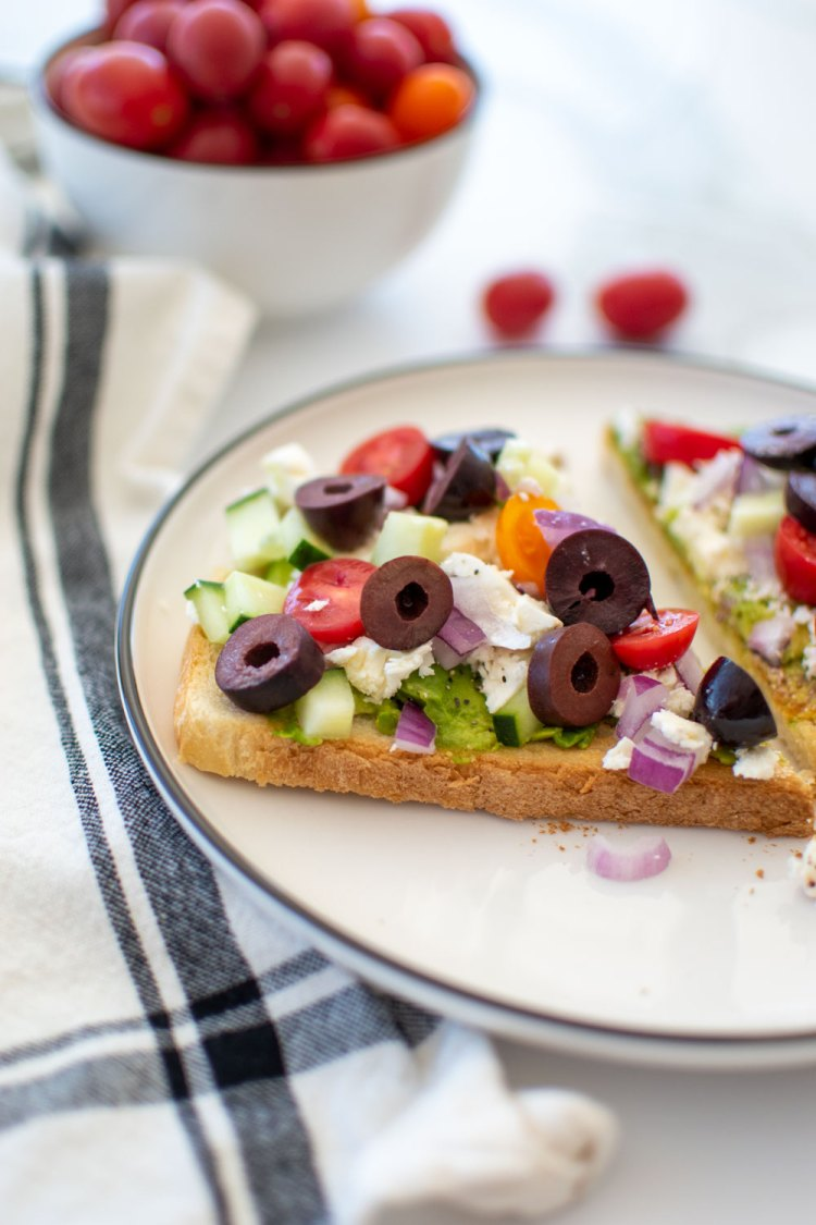 Easy and delicious healthy Greek Avocado Toast recipe. This healthy breakfast or lunch recipe is loaded with Greek inspired veggies and of course a healthy amount of avocado. Get this simple and different avocado toast recipe to make for brunch or lunch! #greek #avocadotoast #greeklunch #greekbreakfast #fetacheese #feta #healthybreakfast #healthylunch