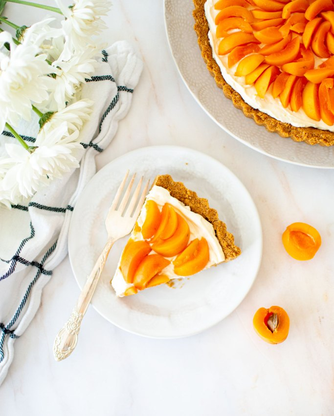 Easy Eggless Apricot Cheesecake Tart Recipe, simple summer dessert recipe that you'll love! Easy and delicious seasonal cheesecake tart. I use fresh seasonal apricots in this recipe to top this eggless cheesecake tart. Homemade graham cracker crust, no bake cheesecake filling, and lots of fresh apricots on top for an easy and amazing summer dessert that everyone will love! #organictart #tartrecipe #apricots #apricottart #cheesecake #cheesecaketart #egglessbaking #egglesstart #egglessdessert