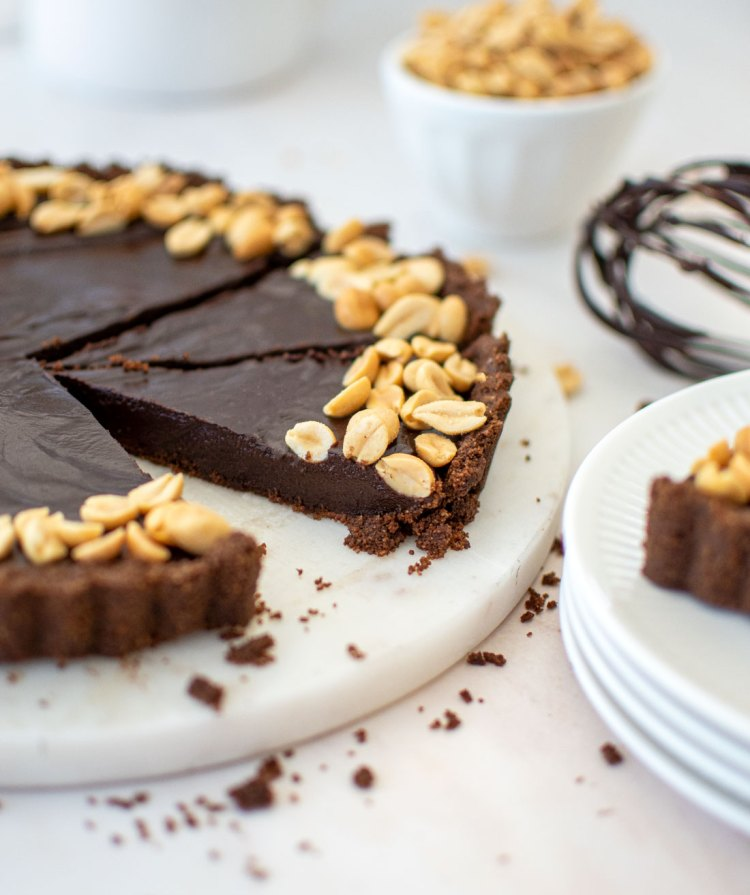 Easy rich, decadent, and impressive Chocolate Peanut Butter Tart recipe. This easy tart recipe is so fancy looking, but it is so easy to make! This is the best recipe to impress guests. A rich chocolate tart with everyone's favorite flavor combination - chocolate and peanut butter! The chocolate graham cracker crust is made from scratch which adds even more flavor to this amazing tart recipe. #easytart #tartrecipe #chocolatepeanutbutter #chocolatepb #chocolatepbdessert #chocolatepbtart #chocolatepeanutbuttertart #chocolatepeanutbutterrecipe #organicbaking #highaltitudebaking #organictart #tartrecipe