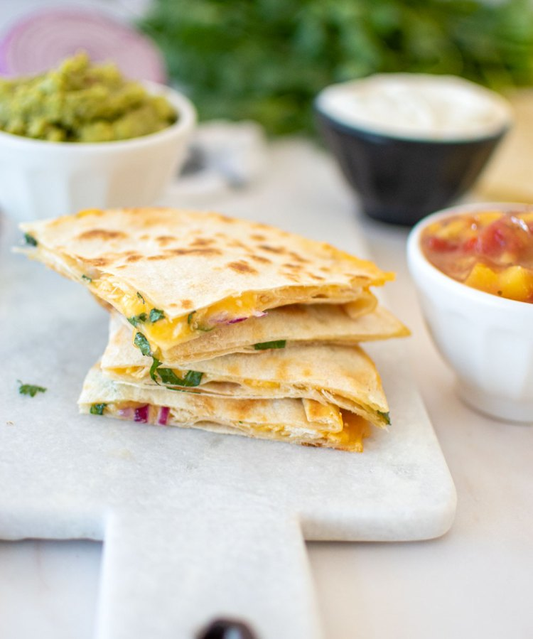 Easy Summer Quesadilla recipe with mango salsa. This light and delicious quesadilla is perfect for summer. Serve it with a sweet mango salsa and my homemade Mango Guacamole. This easy quesadilla uses fully cooked chicken, which you can use leftovers or store bought to make it extra easy! #quesadilla #organicquesadilla #mangosalsa #summerlunch #summerrecipe #healthymexicanfood #healthyquesadilla