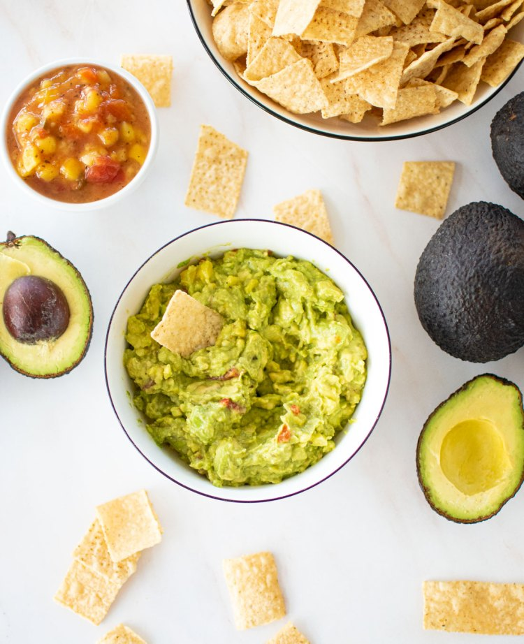 Easy 4 ingredient Mango Guacamole recipe that only takes minutes to make. This super easy homemade guacamole recipe is perfect for summer with the addition of mango salsa. Use this sweeter Mango Guacamole for fish tacos, shrimp tacos, or just to snack on with chips and salsa. #guacamole #mango #mangoguacamole #homemadeguacamole #avocados #organicgaucamole
