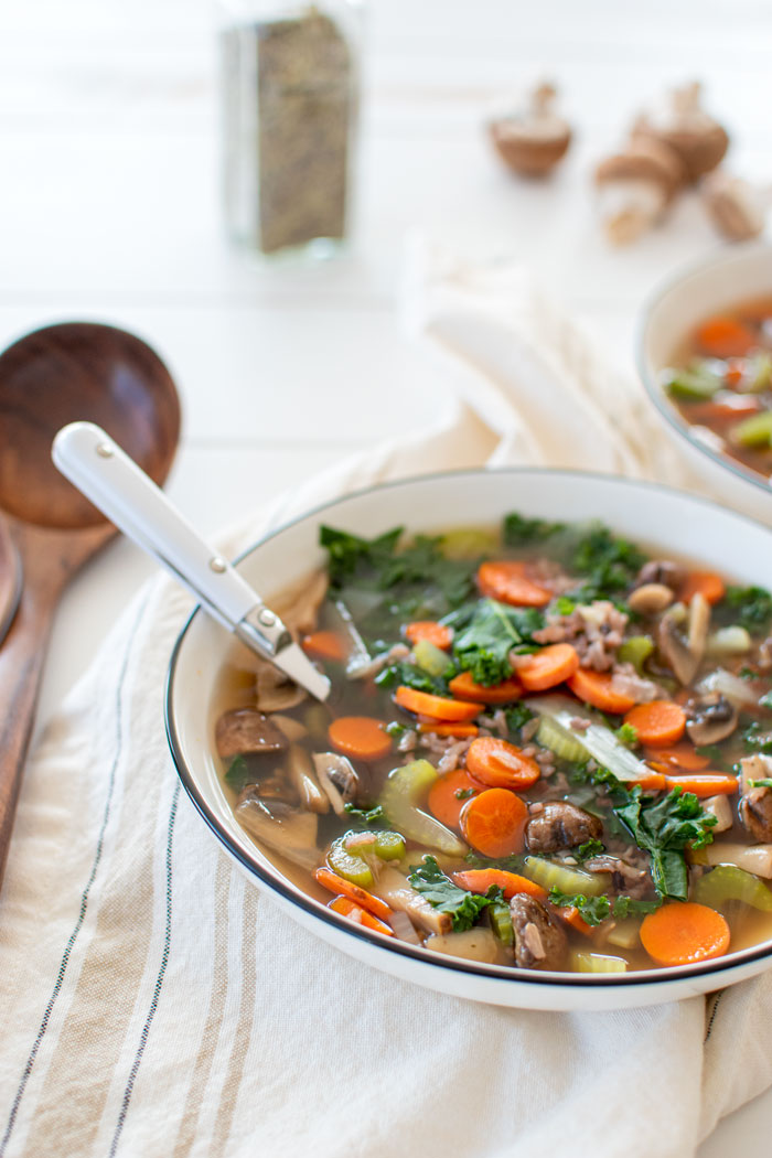 Easy, delicious, healthy, and vegan Mushroom & Wild Rice Soup recipe. This vegetarian and vegan soup recipe is loaded with veggies, which makes it a healthy dinner or side dish! It's naturally gluten free and filled with mushrooms, carrots, celery, onions, kale and herbs #soup #souprecipe #vegan #healthy #healthysoup #vegansoup #glutenfree #souprecipe