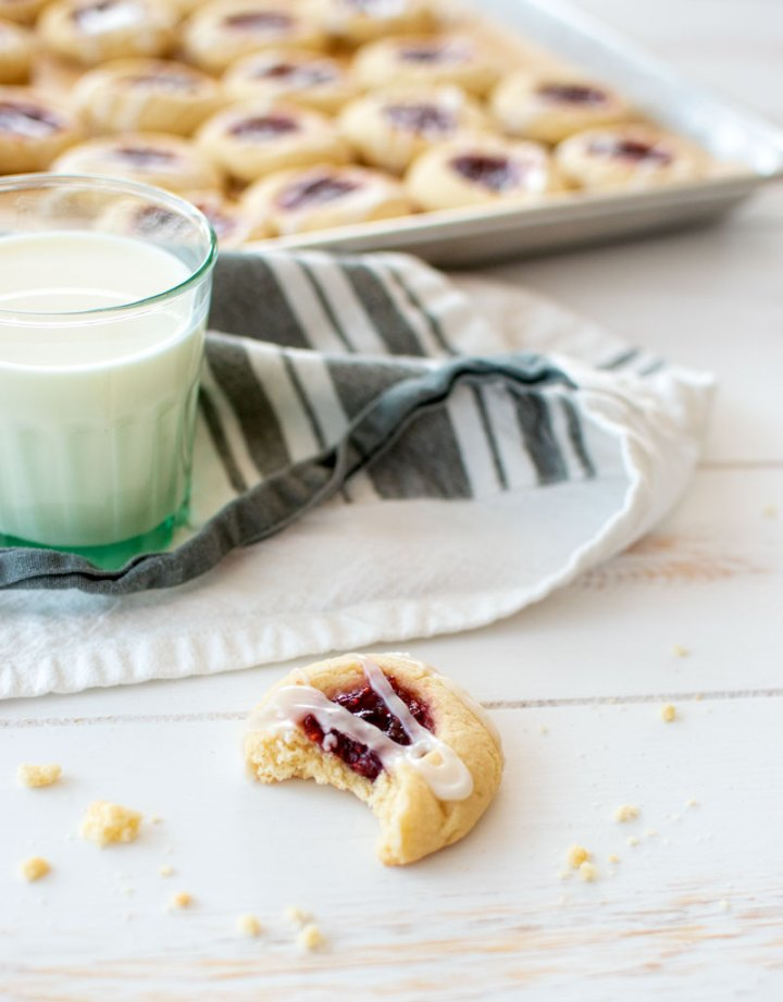 The best Raspberry Thumbprint Cookie recipe, the perfect Christmas cookie recipe! Easy holiday cookie recipe for Raspberry Thumbprints. This recipe can be made gluten free and also at high altitude. Filled with raspberry preserves and topped with a sweet glaze #glaze #thumbprints #cookies #organic #organiccookies #christmascookies #holidaycookies #raspberry #raspberrythumbprints