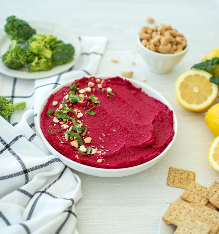 Easy and vibrant beet hummus recipe, Roasted Beet & Garlic Lemon Hummus recipe. This healthy organic hummus is beautiful to display as well as equally delicious to eat! Serve it with fresh veggies, crackers or chips. Roasted beets make for a naturally vibrant bright pink hummus recipe. #organic #hummus #vibrant #naturallycolored #beets #organicbeets #lemonhummus #garlichummus