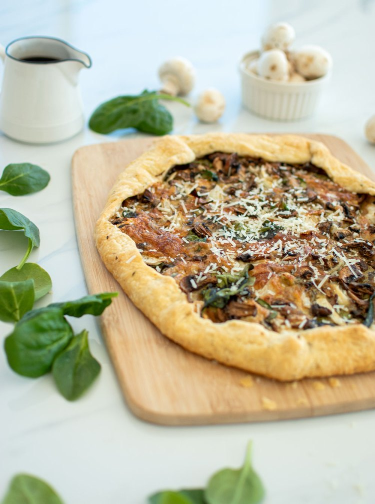 Easy and delicious savory pie recipe, this Spinach Mushroom Galette is sure to wow! A galette is an easy way to make a rustic pie. And this savory galette recipe can be made for breakfast, brunch, lunch, or dinner! Vegetarian and healthy, this Spinach Mushroom Galette recipe is one you'll love! #galette #organic #spinachmushroom #savorypie #savorygalette #brunchrecipe #brunch #dinnerrecipe #diner #lunch