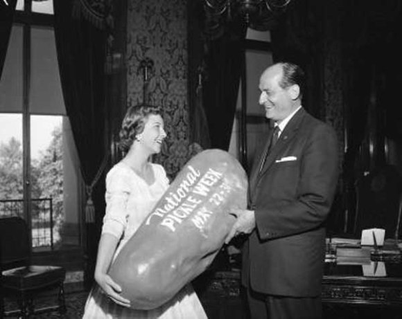 Governor Rosellini is presenting a giant pickle to a gal representing National Pickle Week. National Pickle Week still exists and begins tomorrow, May 15, and ends the 25th. It first began in 1948 and runs 10 days rather than a typical 7 day week and is sponsored by Pickle Packers International.