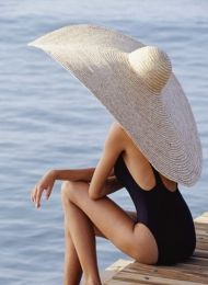 Woman in straw hat sitting on pier Credits: Getty Images David De Lossy