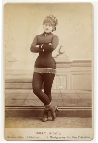 Dolly Adams with fringe at the bottom of a short costume, tights, short-heeled boots topped with fringe, cross at neck, cap. Image: Charles H. McCaghy Collection