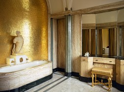 Virginia Courtauld's bathroom, one of many original interiors to survive from the 1930s. The walls are lined with onyx, with gold mosaic tiles in the bath niche.