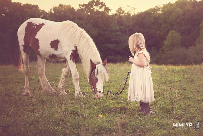 Girl away from camera talking to horse